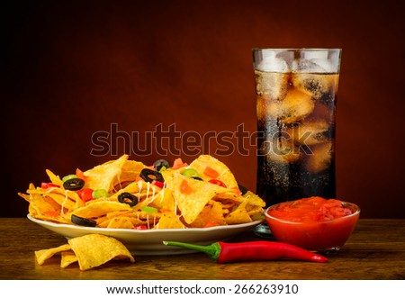 still life with nachos plate, salsa dip and cola drink