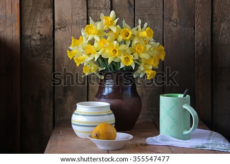 Still life with narcissuses in a clay jug and a lemon on a wooden table.