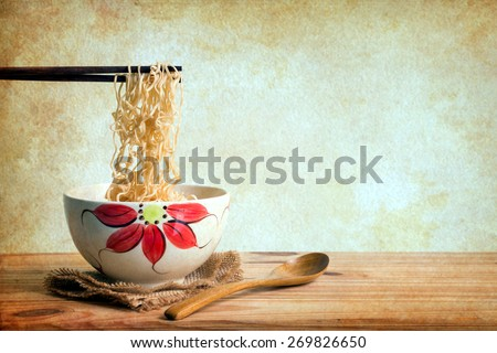 Still life with noodles in a bowl on a wooden table over grunge background - stock photo