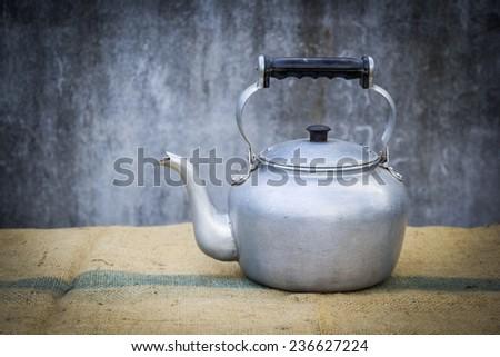 still life with old aluminium kettle - stock photo