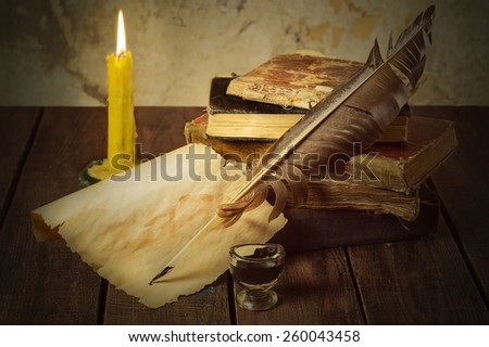 Still life with old books, candle, pen, ink and paper on wooden background. Selective focus. Toned photo - stock photo