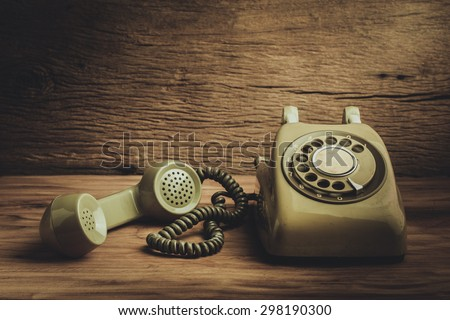 Still life with old green telephone on wooden table - stock photo