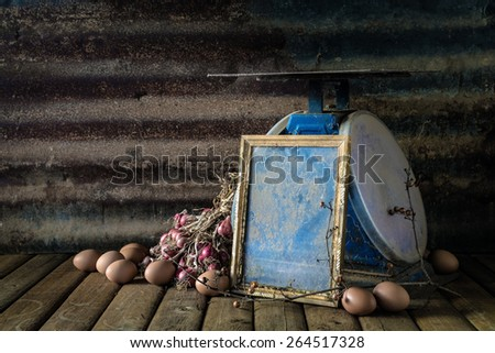 Still life with old photo frame, egg, onion and old blue scales on wood table and rusty steel plate background - stock photo