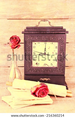 Still life with old retro clock on wooden background - stock photo