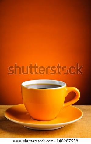 still life with orange espresso coffee cup - stock photo