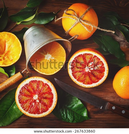 Still life with orange fruit and green leaves on wooden table. Top view. Instagram color effect. - stock photo
