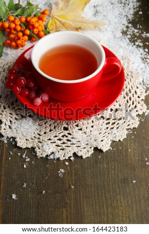Still life with  orange viburnum  tea in cup, berries and snow, on  wooden background