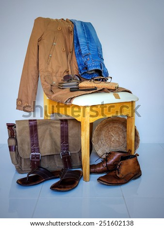 still life with overcoat, boots, jeans and accessory on wooden chair over grunge background ,casual vintage style. - stock photo