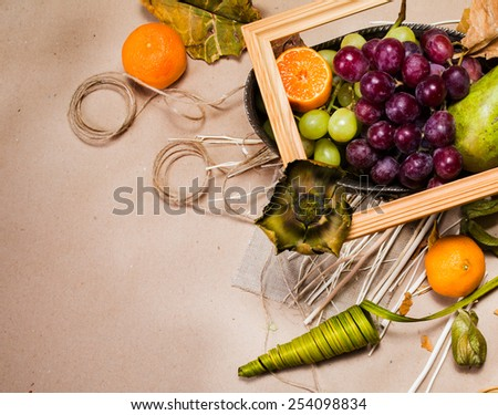 Still life with pears, apple, grapes, tangerines and physalis with dry leafs, twine, decorations, empty wooden frame and silver bowl on light brown paper. View from the top - stock photo