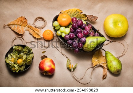 Still life with pears, apple, grapes, tangerines, physalis and pomelo with dry leafs, twine, decorations and silver bowls on light brown paper. View from the top - stock photo