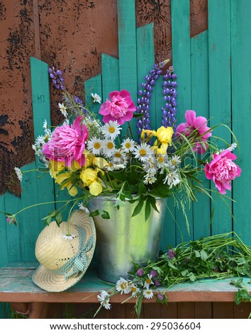 Still life with peony and daisy flowers in a bucket and green straw hat, summer vintage background - stock photo