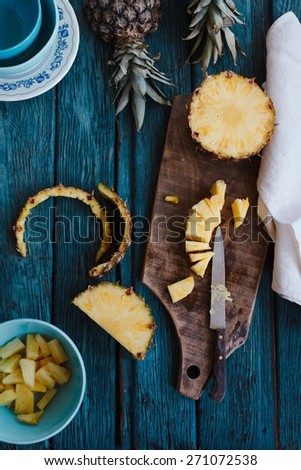 Still life with pineapple on cutting board and blue plates over on vintage background. Preparing  salad fruits exotic. Top view. - stock photo