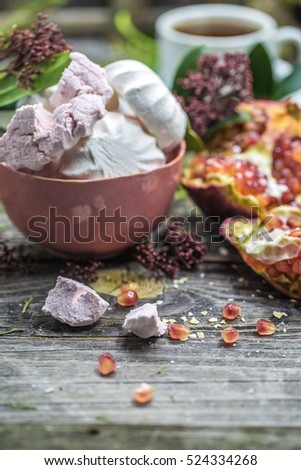 still life with pink marshmallows in the bowl and an open pomegranate on wooden background