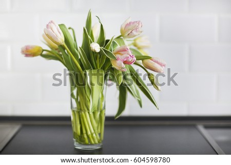 Still life with pink tulips bouquet in glass vase on the kitchen