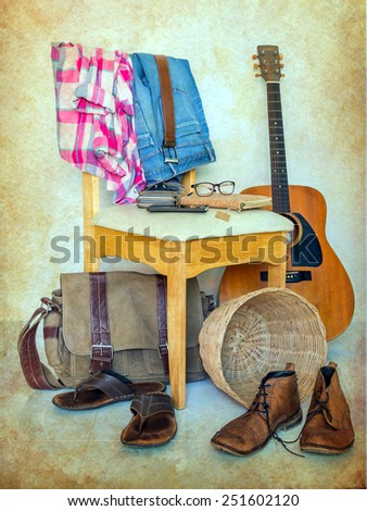 still life with plaid shirt, boots, accessory, and jeans on wooden chair over grunge background, casual vintage style. - stock photo