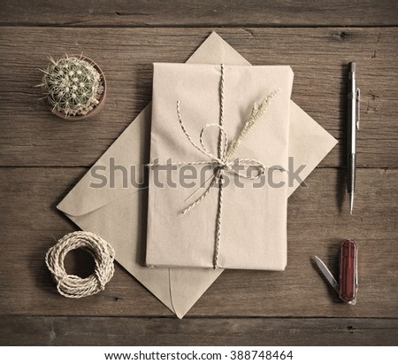 still life with postal parcel wrapped in brown paper and the contents of a workspace composed. Different objects on wooden table. sepia filter effect.Flat lay - stock photo