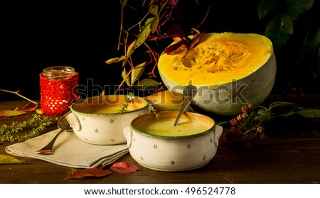 Still life with pumpkin,pumpkin soup and berries and candle