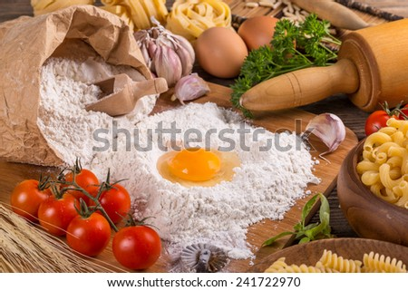 Still life with raw homemade pasta and ingredients for pasta  - stock photo