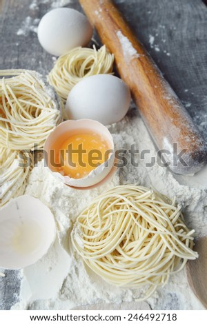 still life with raw homemade pasta and ingredients for pasta.process of cooking pasta - stock photo