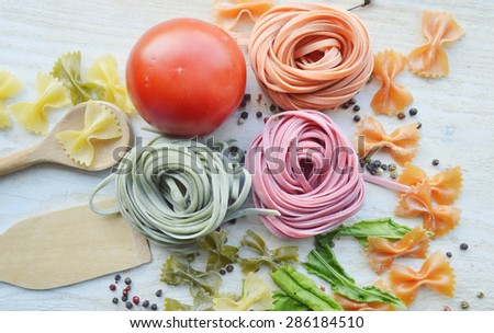 still life with raw homemade pasta and ingredients for pasta.process of cooking pasta.natural dyes for pasta (tomato, spinach, carrots) - stock photo