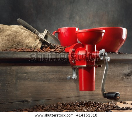 Still-life with red coffee mill and coffee beans on wooden table - stock photo