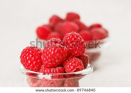 Still life with red raspberry and glass bowl on gray linen table cloth, copy space design ready - stock photo