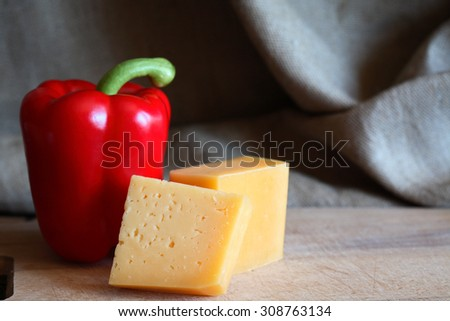 Still life with red sweet pepper near cheese on wooden board - stock photo