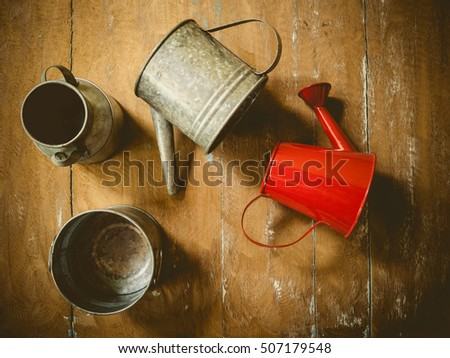 Still life with red watering pot on wooden background