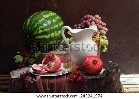 Still-life with red wine, a pomegranate, grapes and a water-melon - stock photo