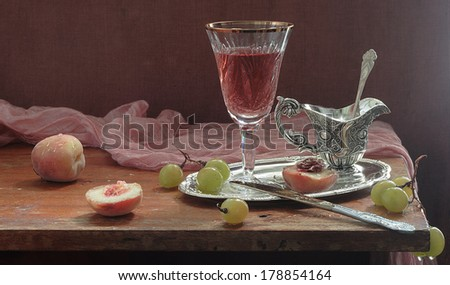 Still-life with red wine and fresh peaches, fragrant red wine in a beautiful wine glass both fresh sweet peaches and juicy ripe grapes