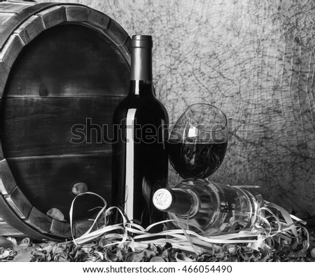 Still life with red wine and heart on a barrel. Black - white.