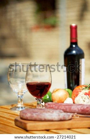 Still life with red wine and meat on table outdoors