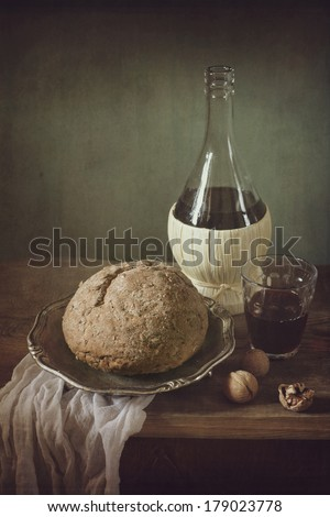 Still life with red wine, bread and walnuts - stock photo