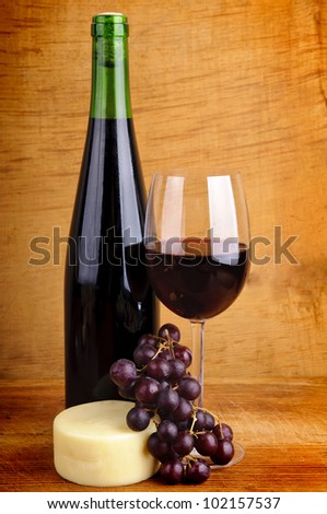still life with red wine, cheese and grapes