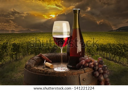 still life with red wine on background vineyard - stock photo
