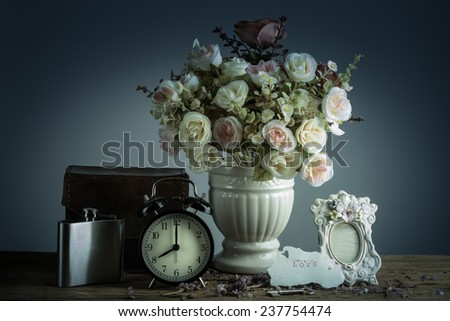 Still life with retro clock and flowers, flake, and love letter on wooden table - stock photo