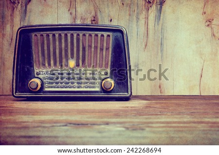 still life with retro radio on the floor over wooden background - stock photo