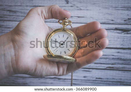 Still life with retro watch on is wooden background - stock photo