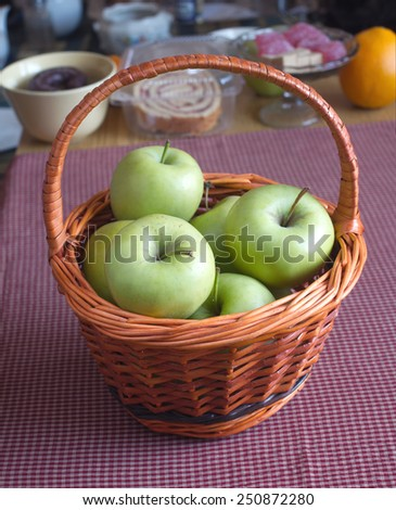 Still life with ripe green apples in brown wicker basket on red tartan cloth on kitchen desk closeup - stock photo