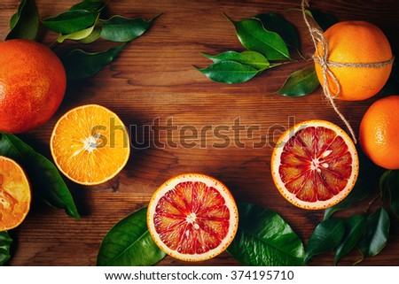 Still Life with Ripe Juicy Citrus Fruits on Wooden Background. Vibrant Colors, Space for Text. View from Above. - stock photo