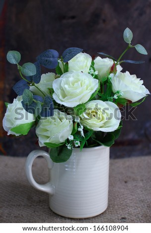 Still life with rose flower in white vase on sackcloth - stock photo