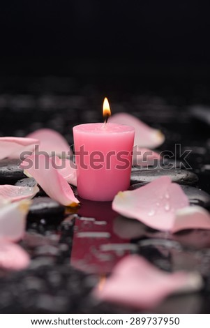 Still life with rose petals, candle and wet stones - stock photo