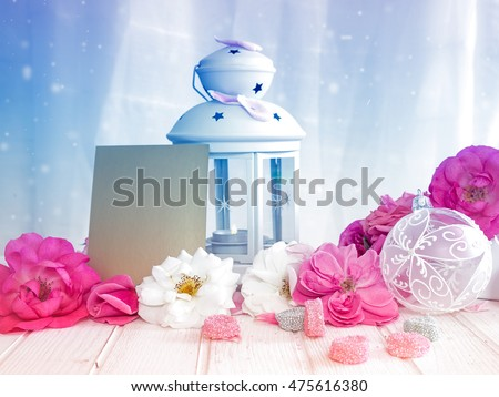 Still life with roses and a white lantern with empty greeting card