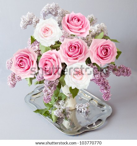 Still life with roses and lilac flowers bunch on silver tea tray on artistic background - stock photo