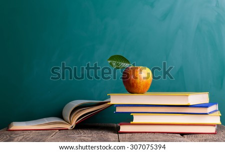 "Still life with school books and apple against blackboard with ""back to school"" on background - stock photo"