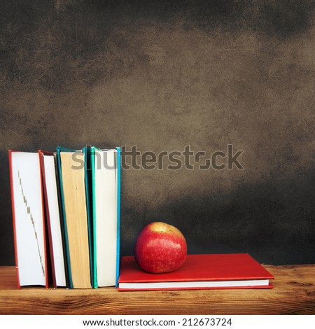Still life with school books and apple against clean black blackboard on background