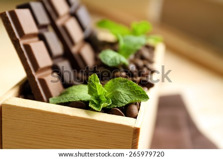 Still life with set of chocolate in wooden box of coffee grains, closeup - stock photo