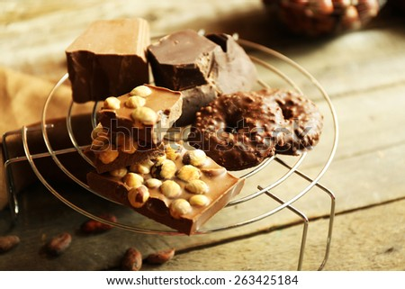 Still life with set of chocolate with nuts on metal stand, closeup - stock photo