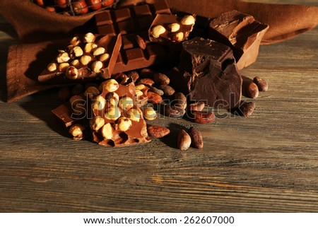 Still life with set of chocolate with nuts on wooden background - stock photo