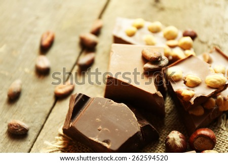 Still life with set of chocolate with nuts on wooden table, closeup - stock photo